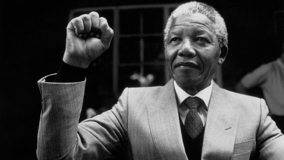 [Image description: Black and white image of Nelson Mandela wearing a suit and holding his fist in the air.] via Google Images
