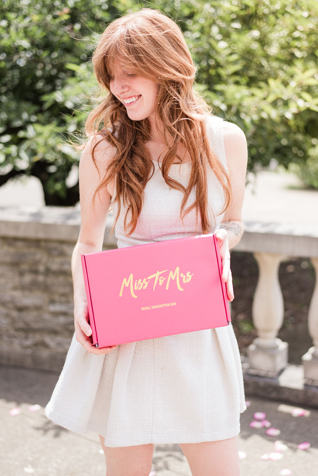 """[Image description: a woman in a dress holding a pink box that says """"Miss to Mrs] Via MissToMrsBrideBox"""