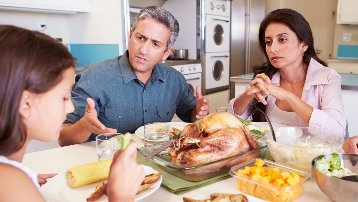 [Image description: A concerned mother and a father seated at the dinner table with their daughter. ] via Alamy