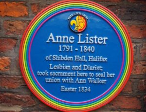 [Image description: blue circular plaque with a rainbow circumference mounted on a brick wall and commemorating Anne Lister (1791-1840).] via BBC.com