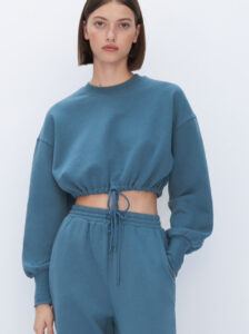 White woman modeling a blue/green sweatsuit. The top is cropped with an adjustable drawstring