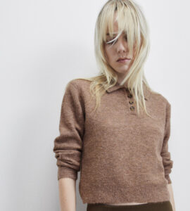 White woman with blonde hair and bangs wearing a taupe brown knit polo sweater with three buttons at the top.