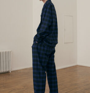 White man a dark blue and black flannel pajama set.