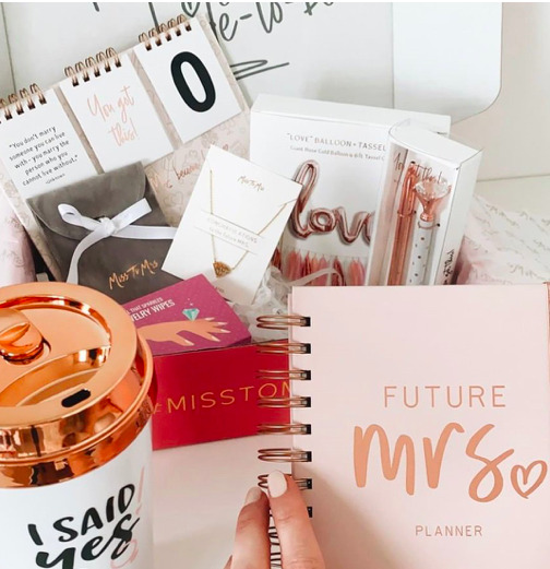 [Image description: a wedding box with a pink notebook and pen, a calendar, stickers, and a reusable cup] Via Wedding Forward