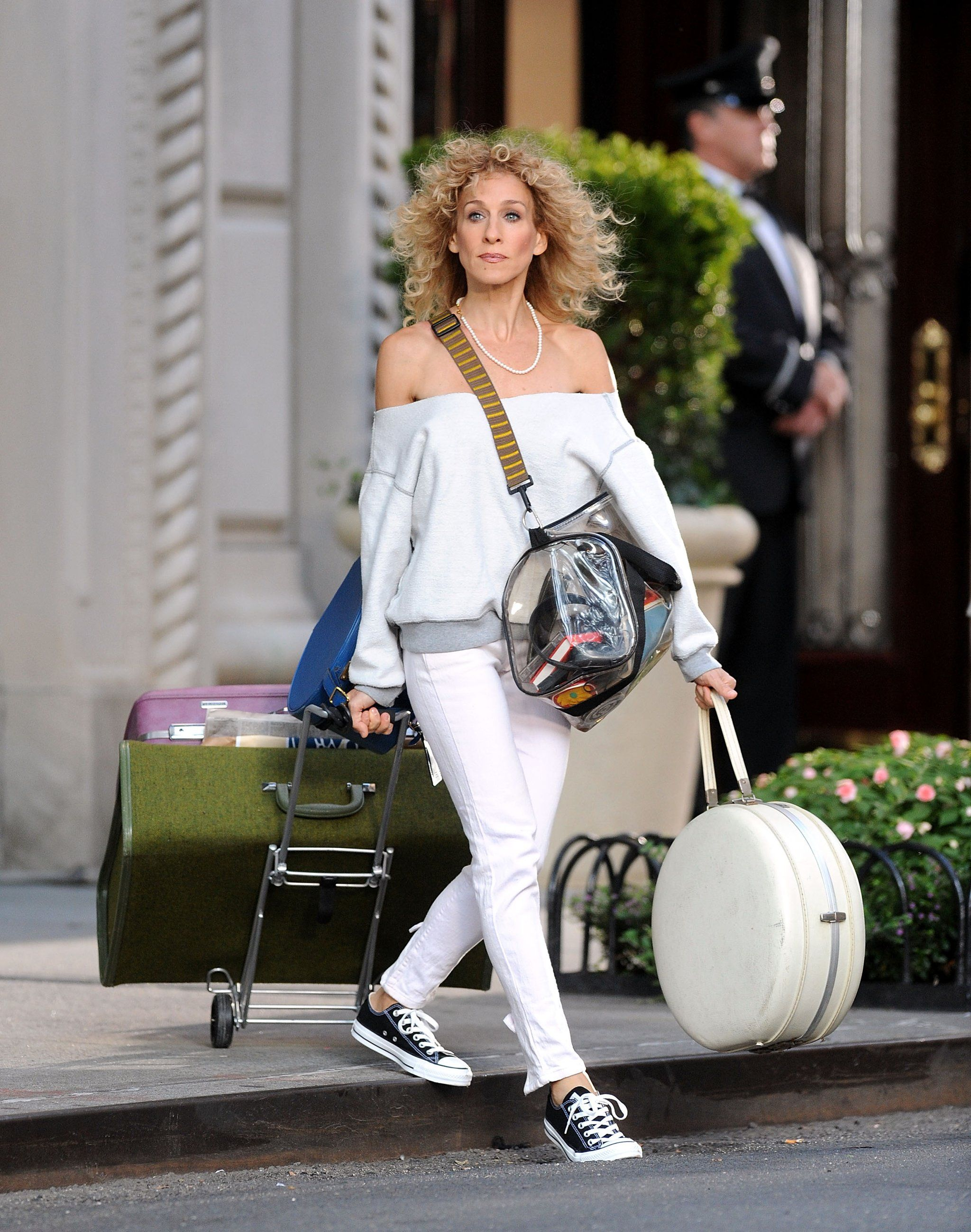 Carrie Bradshaw wearing a white sweater and jeans and black and white sneakers, holding bags and luggage