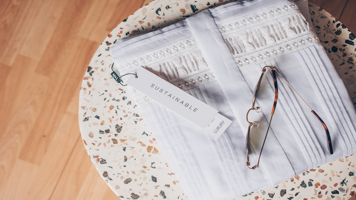 Sunglasses sitting on folded white shirt with a tag that says 'sustainable', on top of terrazzo side table