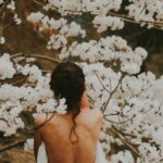 [Image description: The back of a woman's body against a tree filled with flowers.] Via Rodolpho Sanchez on Unsplash