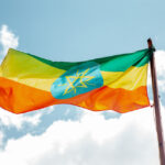 The Ethiopian flag, in front of a cloudy blue sky