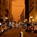 [A firefighter walks across the street under the smoky skies from wildfires in San Francisco] via unsplash