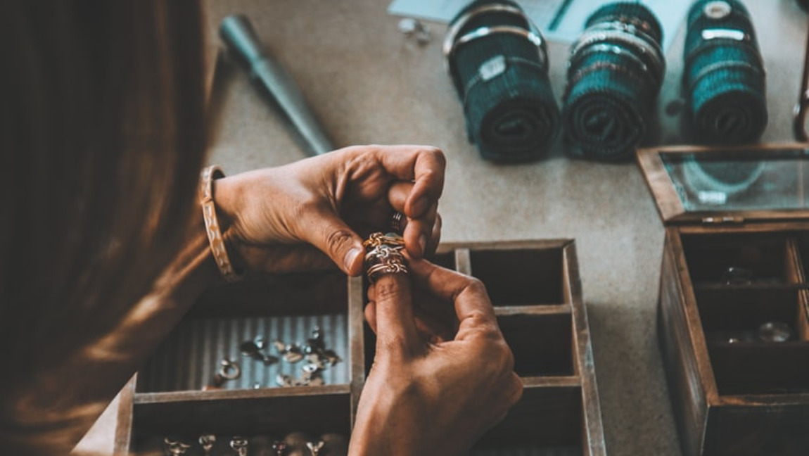 A woman wearing rings on her fingers. There is a woodeen jewelry box and around it are three green cloths that are are being used to keep bracelets. [Via Unsplash]