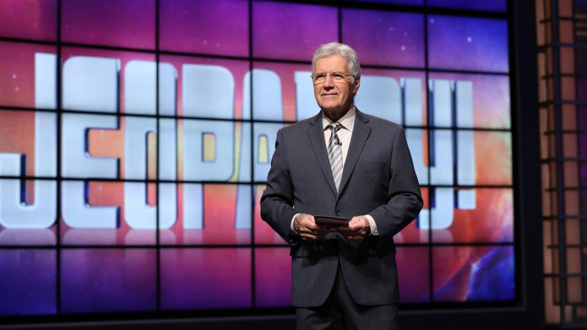 Alex Trebek wearing a suit, standing in front of a screen reading 'Jeopardy!'