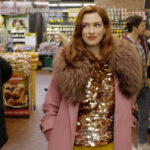 [Image description: A scene from 'Modern Love' where Anne Hathaway is seen walking the store aisle dressed in evening clothes] via Amazon Prime Video