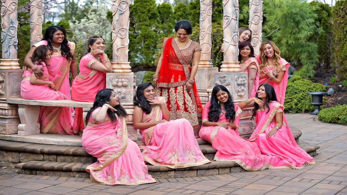 Group of women in pink saris sitting around bride wearing red wedding lehenga