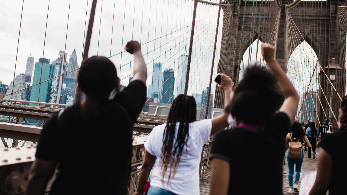[Image description: Three women marching on a bridge while holding up Black power fists.] Via free photos on Pexels