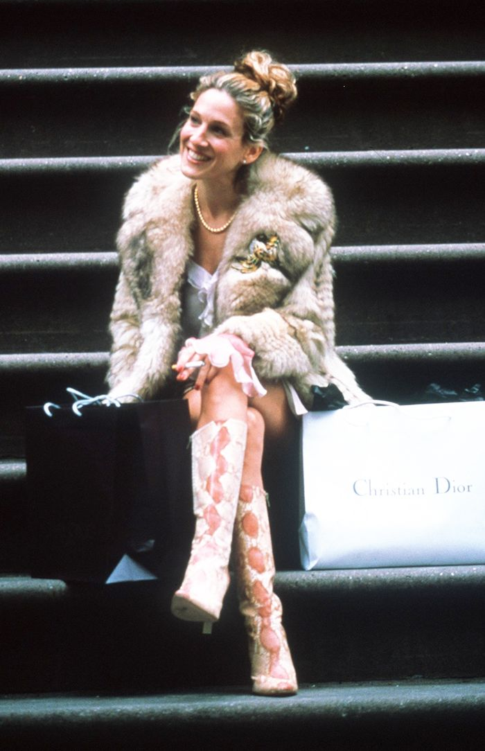 Carrie Bradshaw sitting on steps wearing a fur coat and snakeskin boots. Shopping bags are beside her