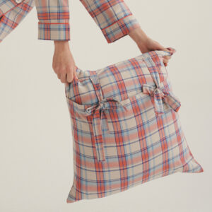 A cushion with a coral flannel pattern being held by a person wearing pajamas that math the cushion pattern.
