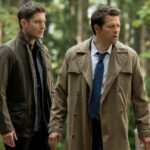Jensen Ackles as Dean and Misha Collins as Castiel standing in the forest.