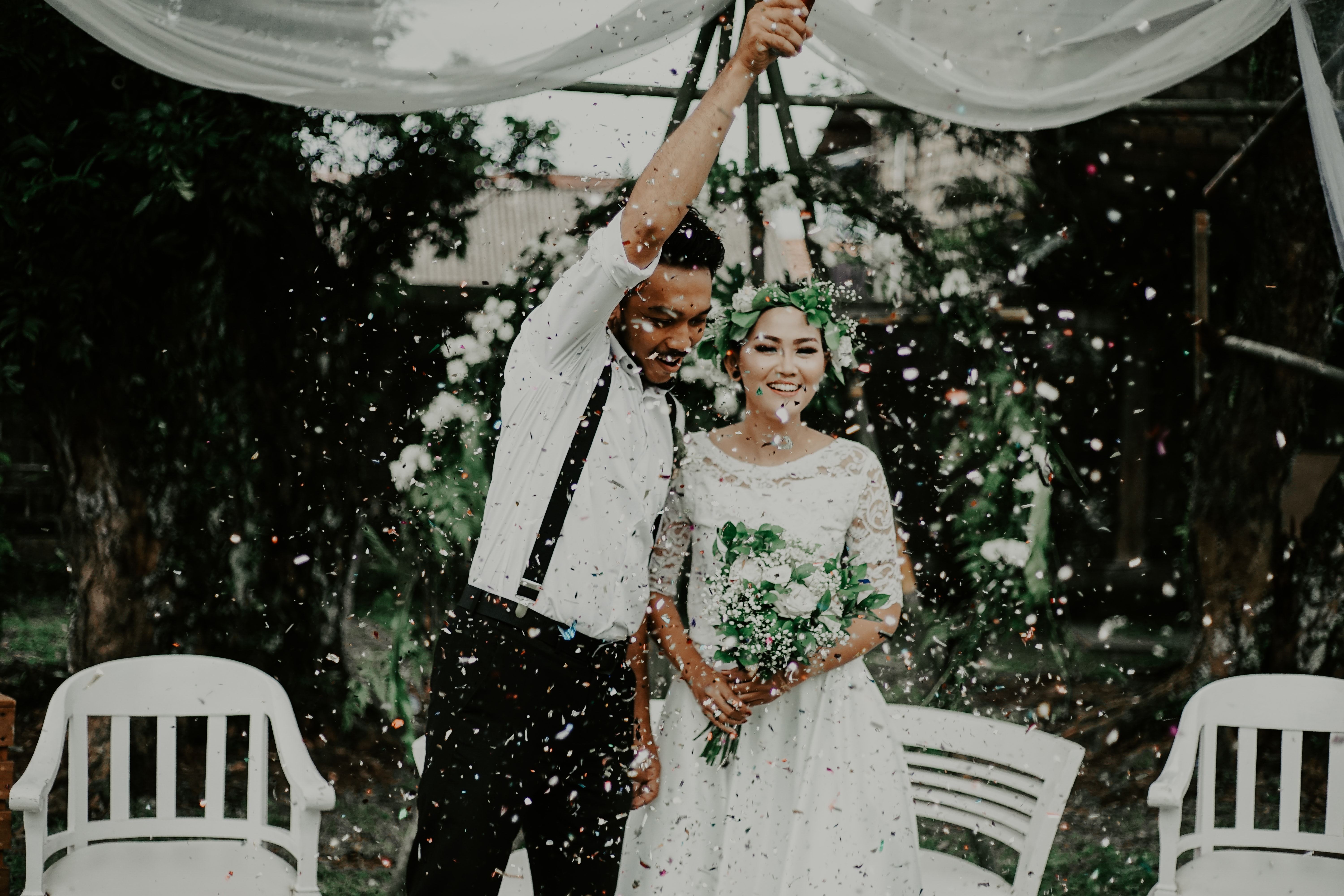 [Image description: a bride and groom surrounded by flying petals and confetti] Via Unsplash