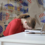 [Image description: A woman in a red sweater sits at her desk with translucent voting stickers around her.] Via Pexels and Unsplash.