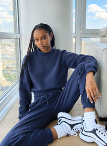 Black woman with braids wearing a dark blue sweatsuit with white long socks and white sneakers.