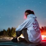 [Image Description: A girl in a white hoody sitting on top of a car watching the stars and the night sky.] Via Unsplash