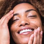 A Black woman with a light brown afro is cupping her face and smiling.