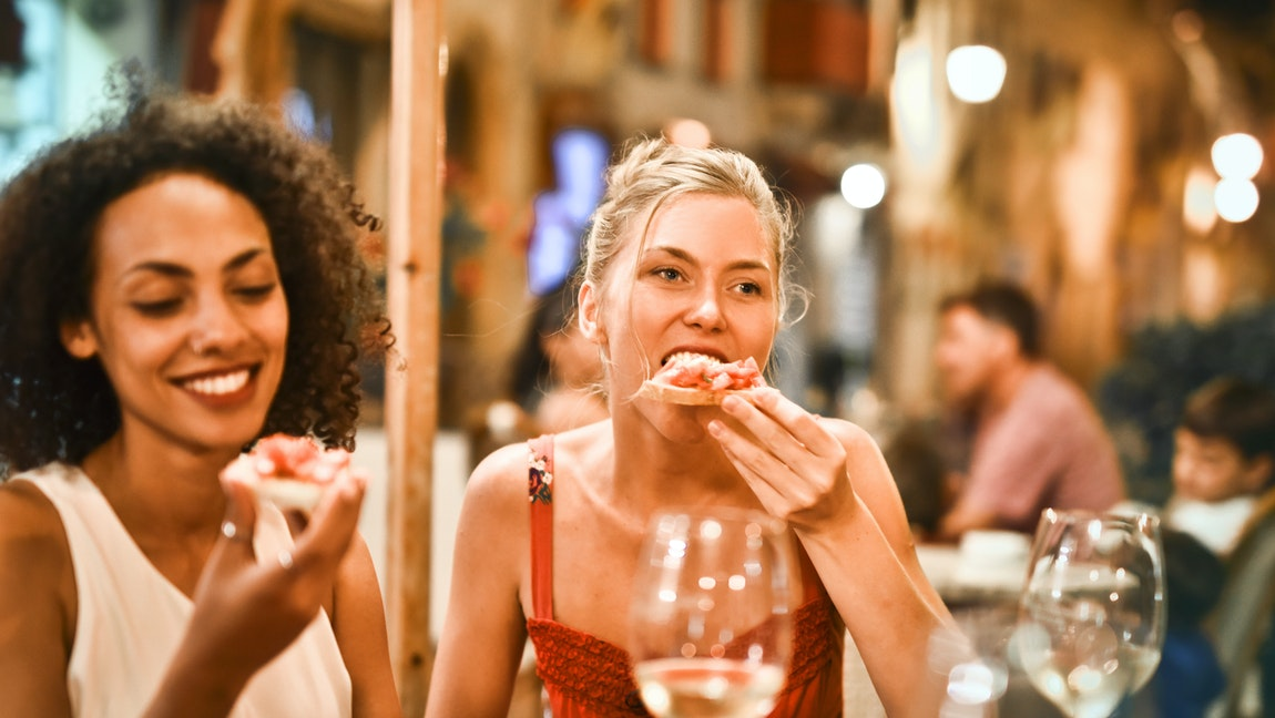 [Image Description: Two women at a restaurant patio eating pizza together.] Via Pexels