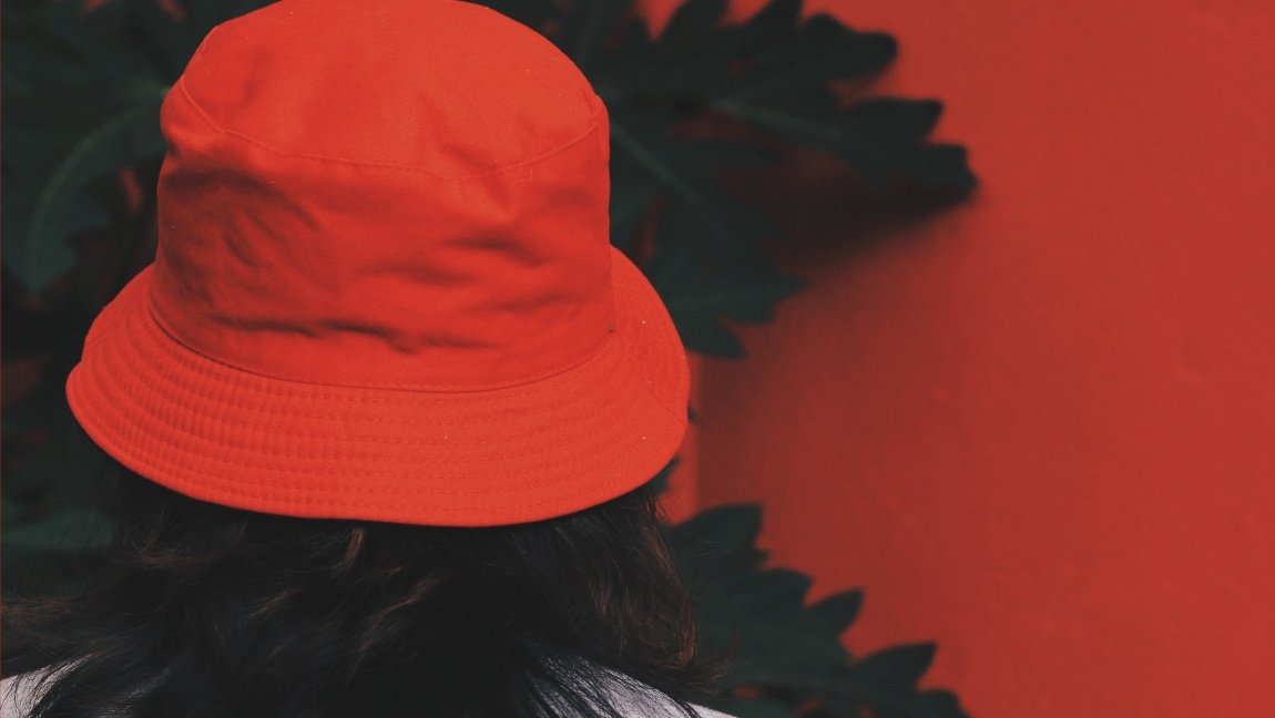 A woman facing away from the camera wearing a bright red bucket hat with short dark hair. In the background there is a dark green tree and a bright red wall.