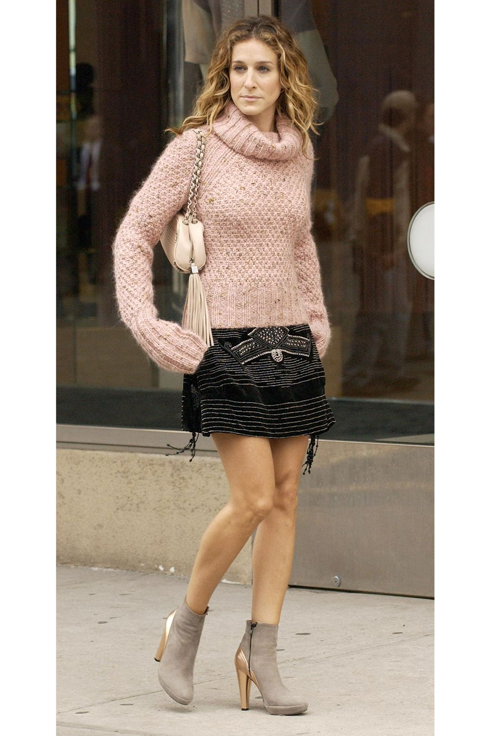 Carrie Bradshaw wearing a pink sweater, black skirt and two-tone ankle-length boots.