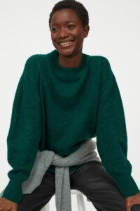 Black woman modeling a dark green sweater while sitting on a stool.
