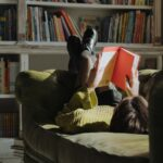 Woman in a yellow sweater lies on a couch, reading in a library.
