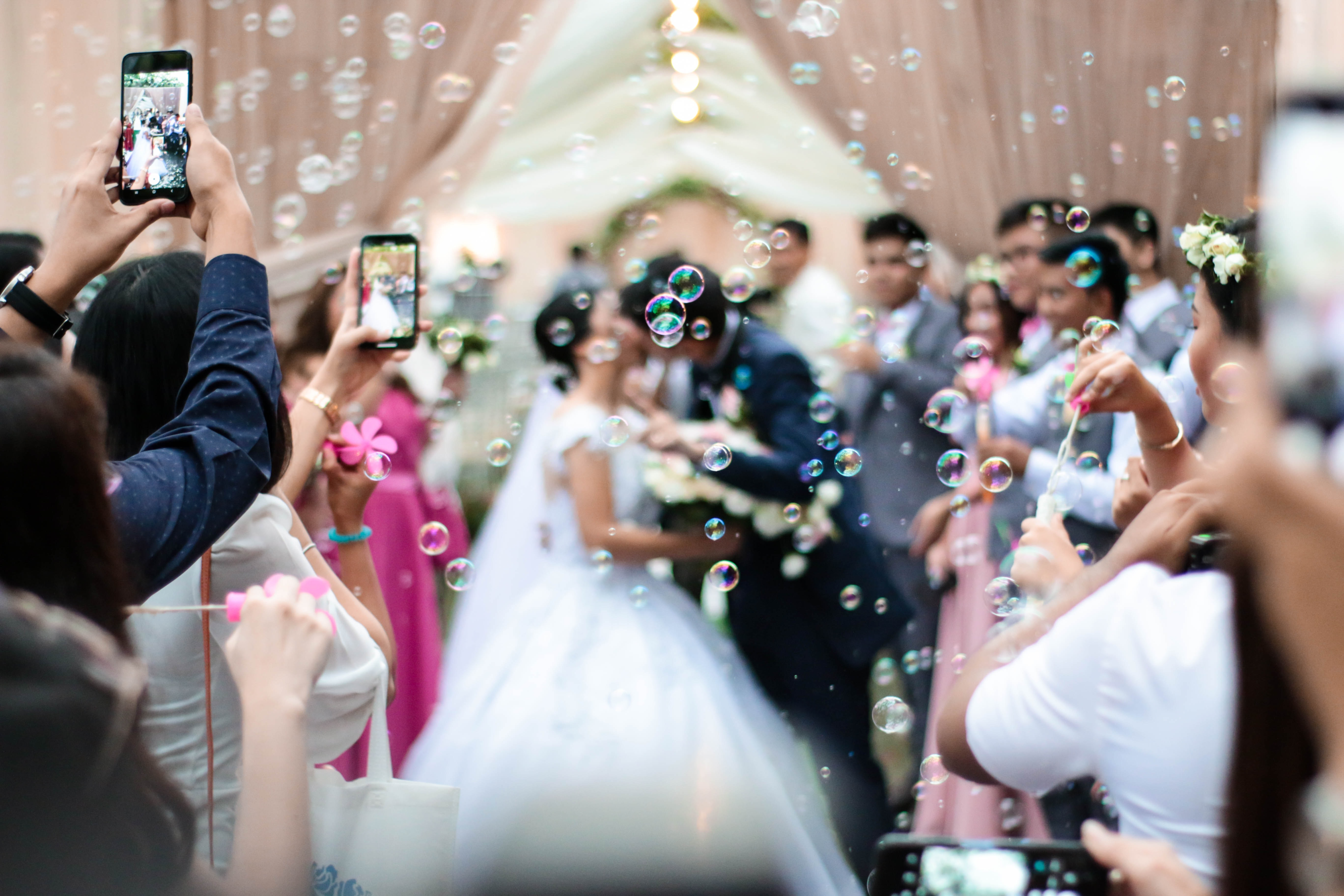 [Image description: various phones take pictures of the bride and groom kissing] Via Unsplash