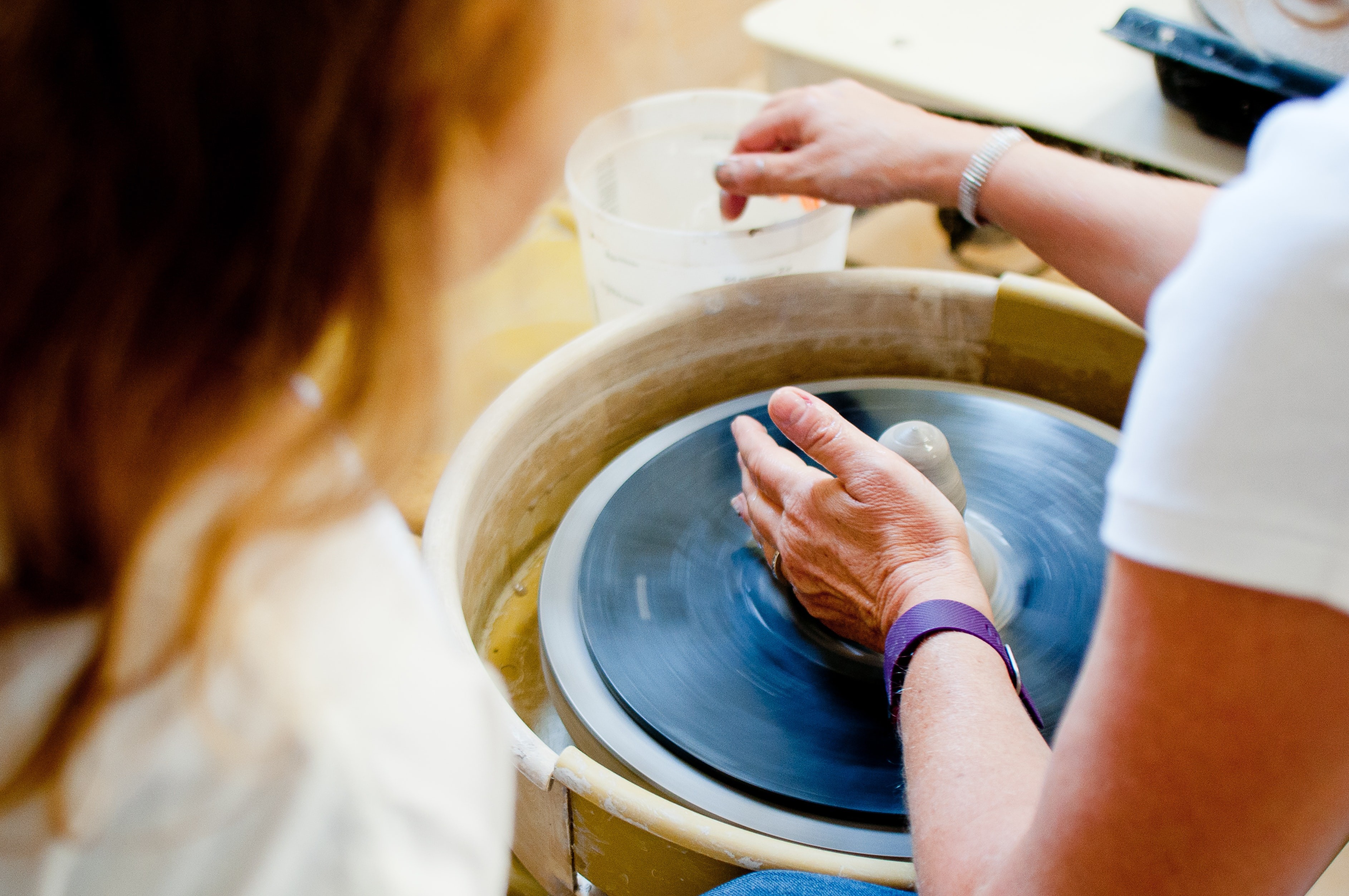 [Image description: a woman spinning a vase of pottery] Via Unsplash
