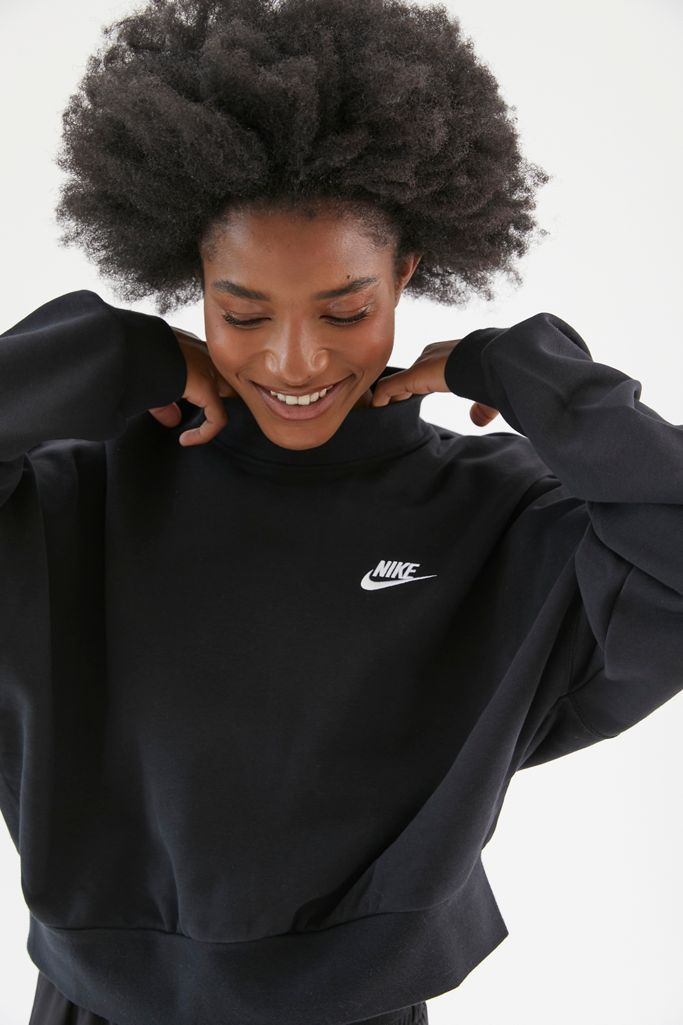 Black woman with an Afro wearing a black Nike crewneck