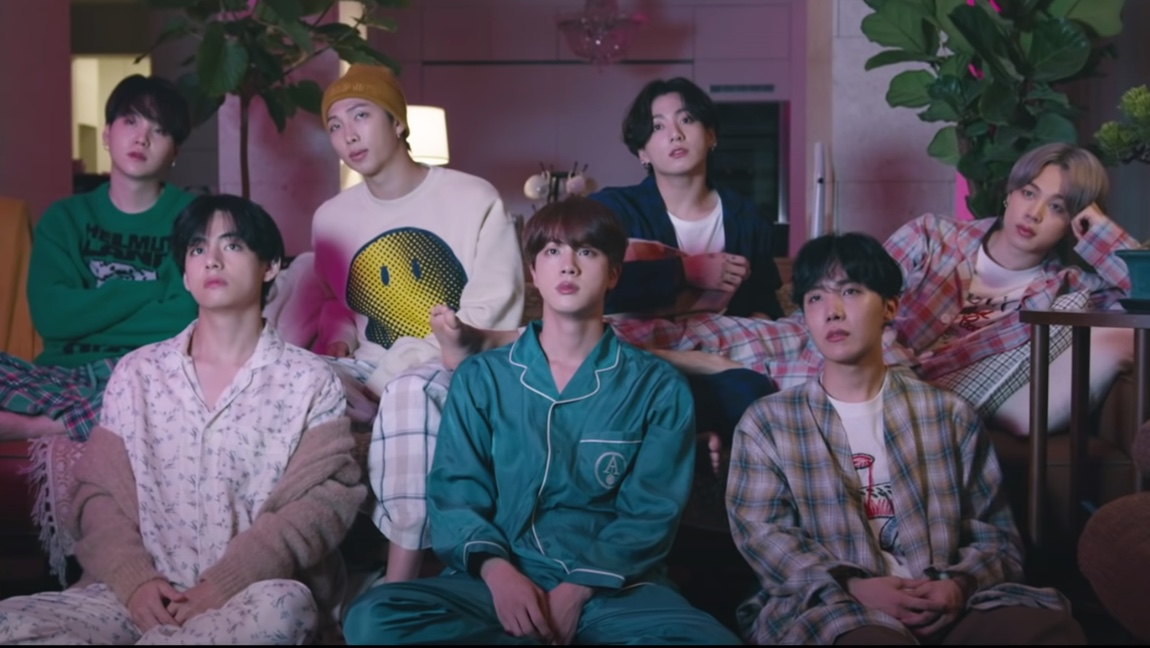 "A picture of BTS from the ""Life Goes ON"" music video. Suga, RM, Jungkook, and Jimin are sitting on a couch, while V, J-Hope, and Jin are sitting on the floor in front of the couch."