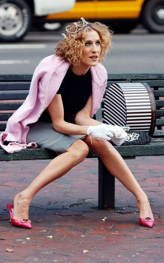 Carrie Bradshaw sitting on a bench wearing a tiara, black top, gray skirt, pink coat and hot pink-pointy heels.