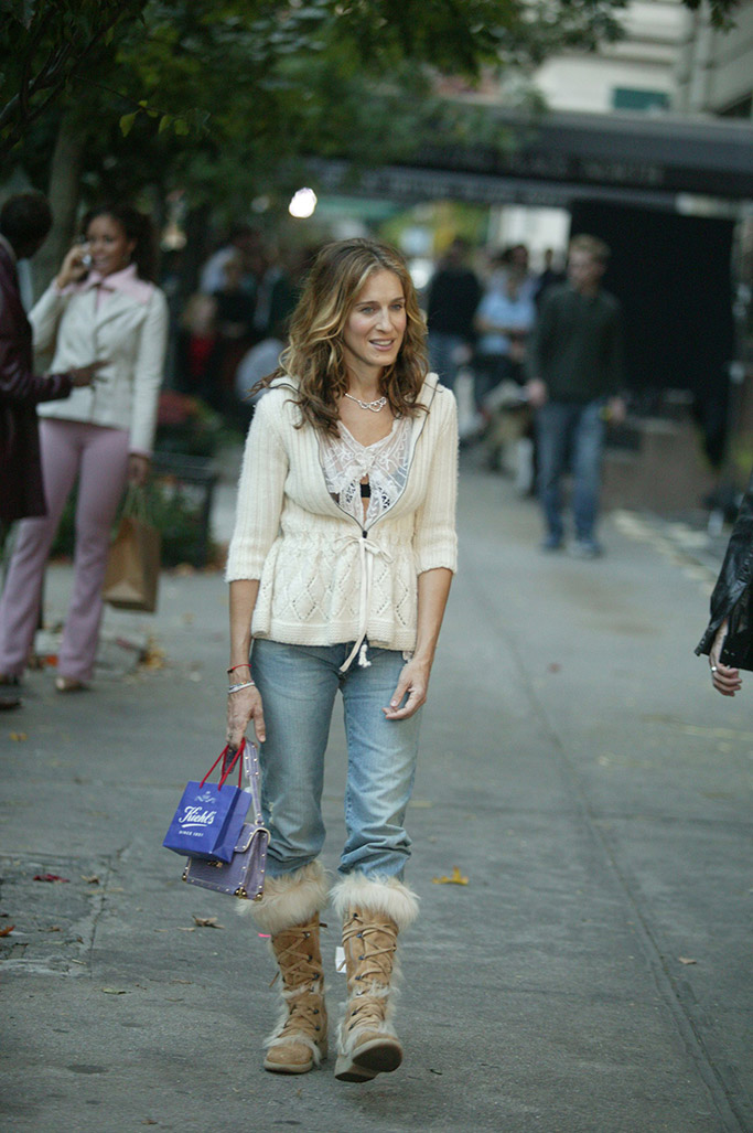 Carrie Bradshaw wearing a white top, jeans, and knee-length furry boots.