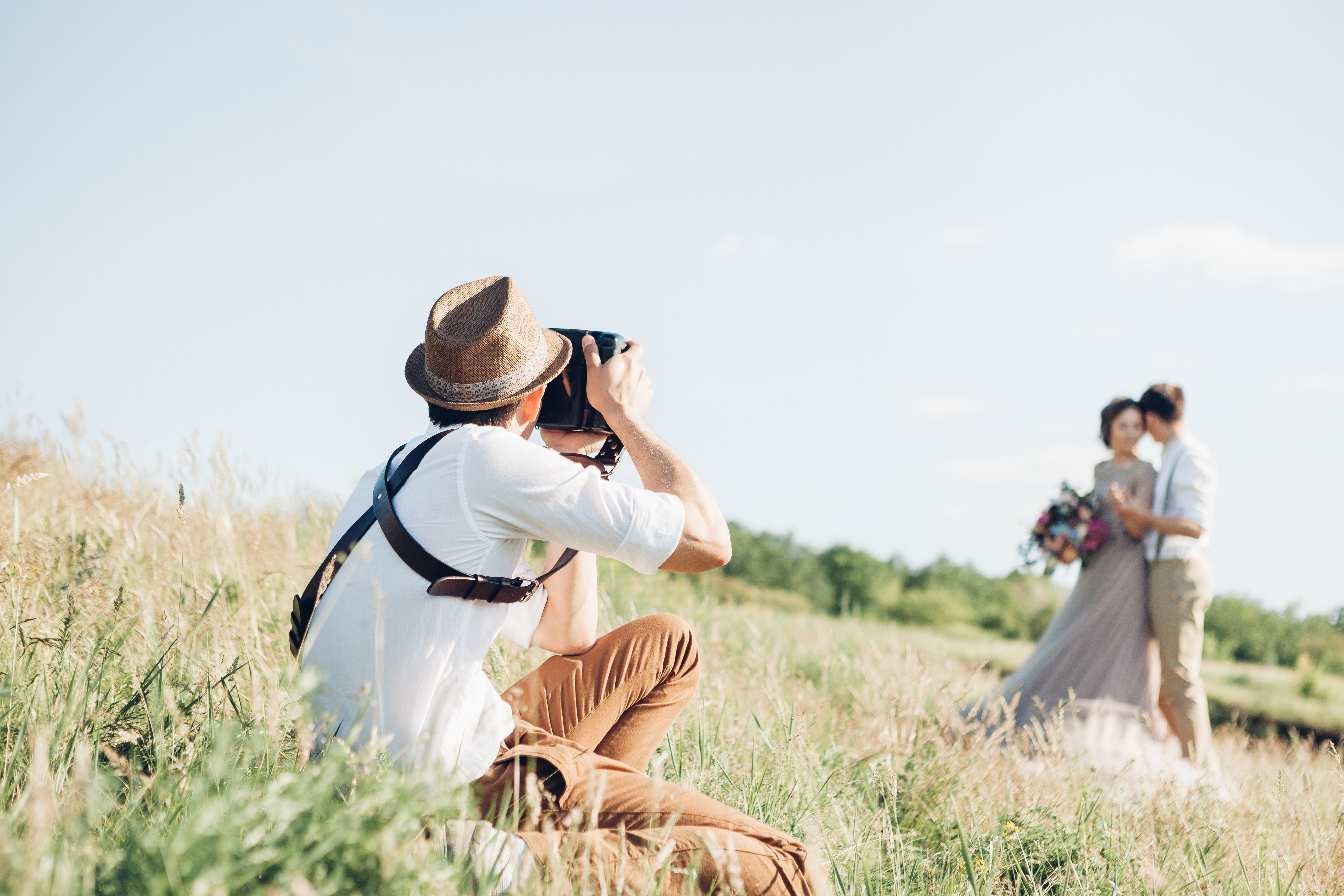 [Image description: a photographer capturing images of the bride and groom] via Wedding Forward