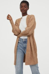 Black woman wearing a long taupe cardigan, white t-shirt, and jeans.