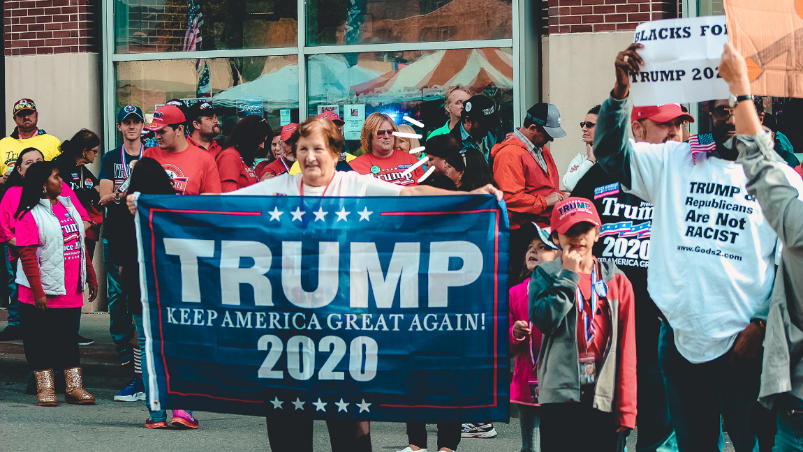 [Image Description: An image from a pro Trump rally with a woman holding a Trump 2020 banner] Via Canva