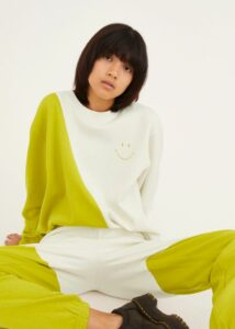 Asian woman wearing a white and lime/yellow sweatshirt with a small smiley face on the top right area of the sweatshirt.