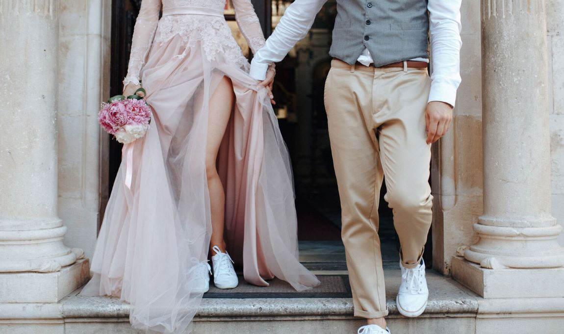 A bride and groom holding hands at their wedding.