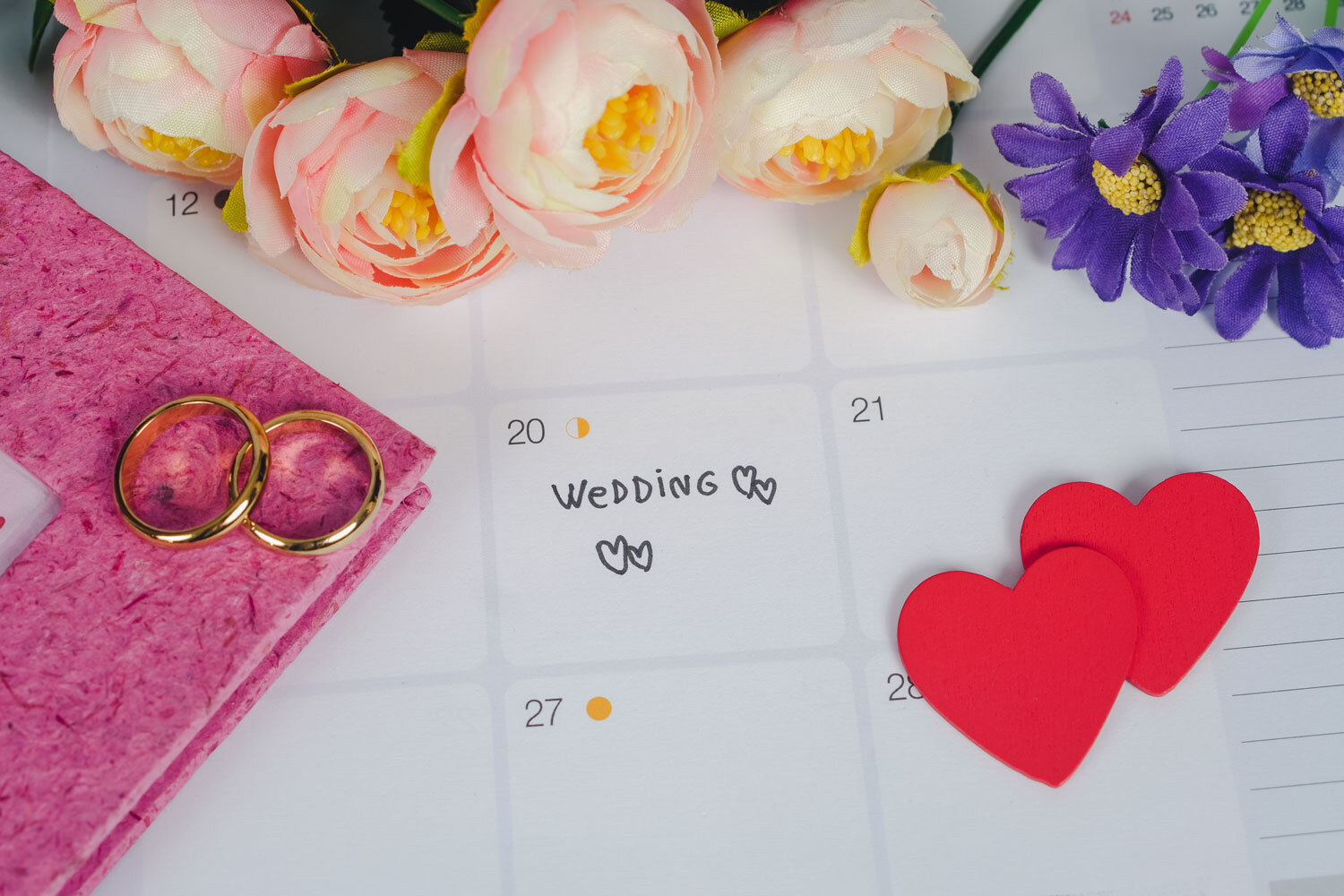 [Image description: a wedding calendar, with roses, hearts, and the rings] Via Unsplash