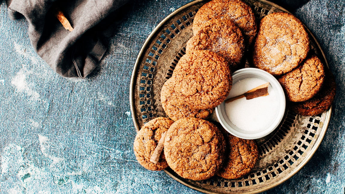 Photo of a plate full of cookies and a small bowl of sugar with a piece of cinnamon with a crumpled apron on the side
