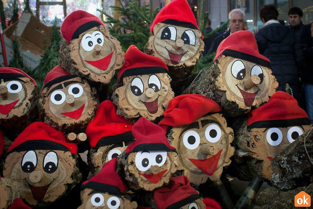A bunch of log faces are pictured together, each bearing a pair of eyes, a nose, and a red hat.