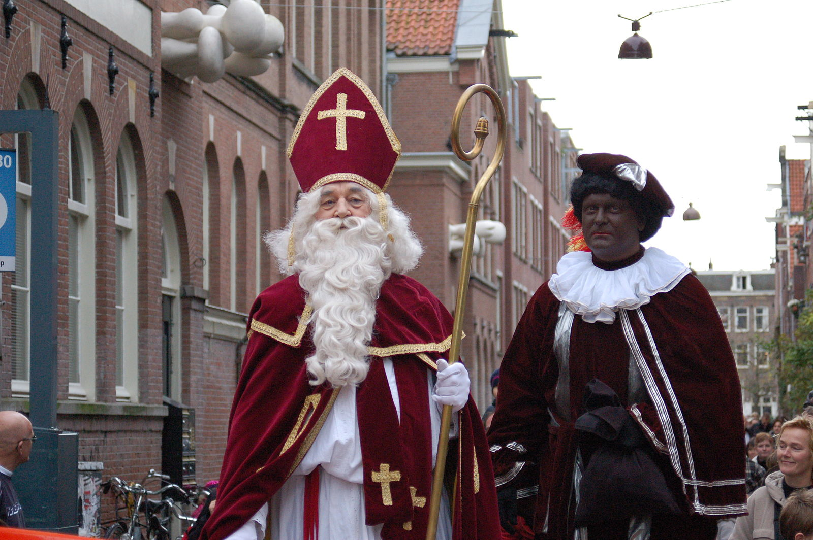 Two people, Sinterklaas (left) and Zwarte Piet (left) appear in costume. Zwarte Piet is played by a person in blackface, dressed in a white fulled collar and maroon garments. Sinterklaas wears red robes and an elaborate headgear, and carries a staff.