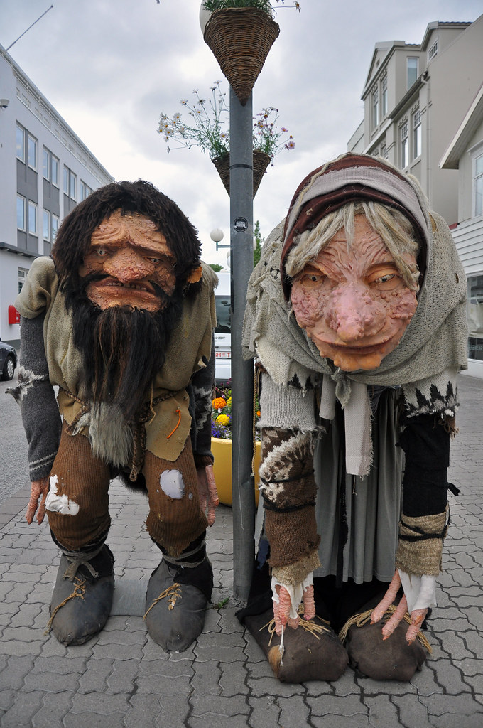 Model figures of Grýla (right) and Leppalúði (left) hanging out on Akureyri's main shopping street, Hafnarstraeti. They are giant-sized with drooping heads and bodies.