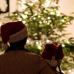 [Individuals sitting around the Christmas tree, with their arms around each other] Via Unsplash.