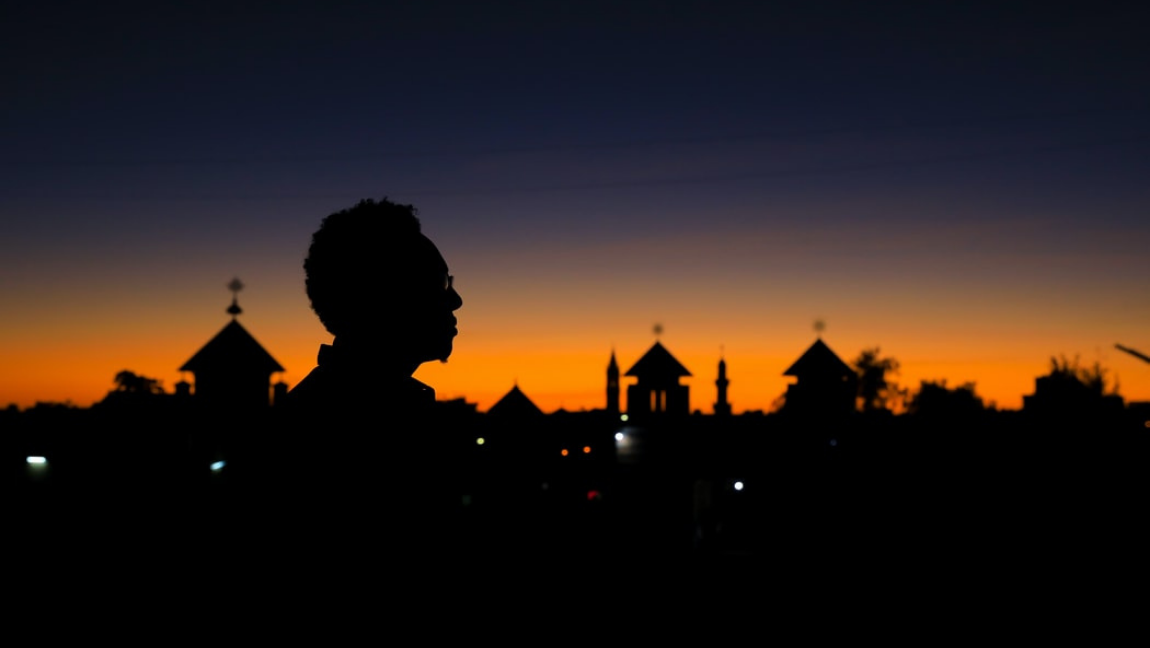 [Image description: sunset silhouette of Director Abraham Wolde in Asmera, Eritrea.] via Unsplash