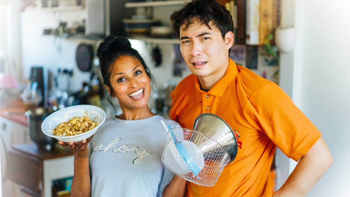 A man in an orange polo looks disgruntled, next to a smiling lady with a bowl of fried rice and a colander